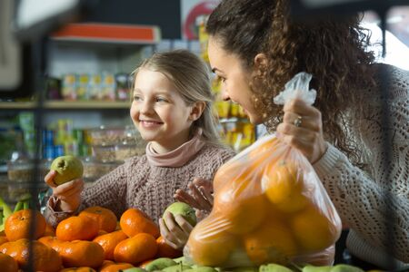 purchasers: smiling mother and blonde daughter buying mandarins in shop Stock Photo