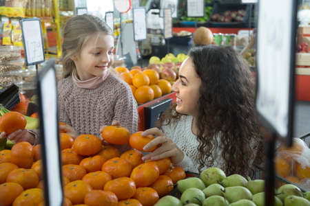citrus family: mother and blonde daughter buying mandarins in shop