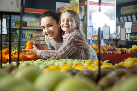 purchasers: portret of young woman with beautiful blonde daughter choosing mandarins at store. Focus on woman