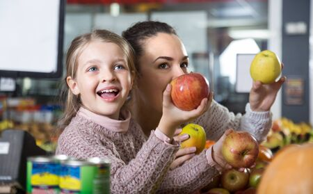 portret of young woman with smiling beautiful daughter choosing apples at store