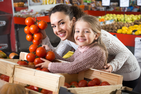 posinive mother and daughter buying tomatoes in shop Standard-Bild