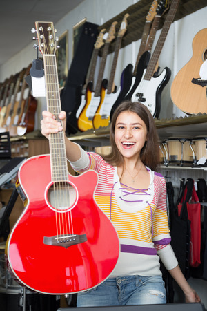 Young female selecting new guitar in store and smiling Stock Photo