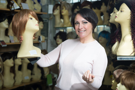 peruke: smiling middle aged female customer holding dummy with wig in hair salon Stock Photo
