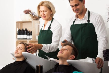 Hairstylists washing the hair of customers at the hairdressing salon Stock Photo