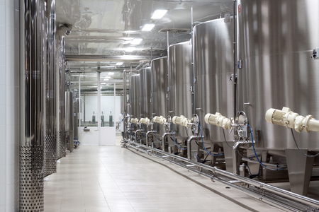 row of arge metal vats for fermentation of winery