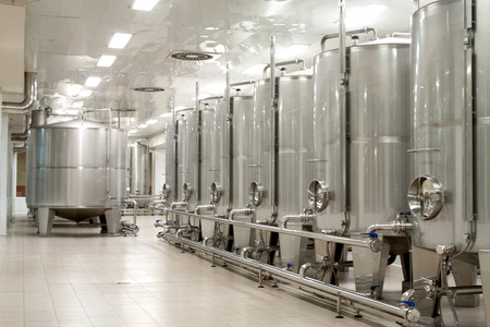 reservoirs: real modern Stainless steel wine reservoirs  in a row inside the modern factory