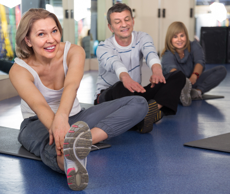 active adult community: successful elderly people doing exercise on mat in modern gym