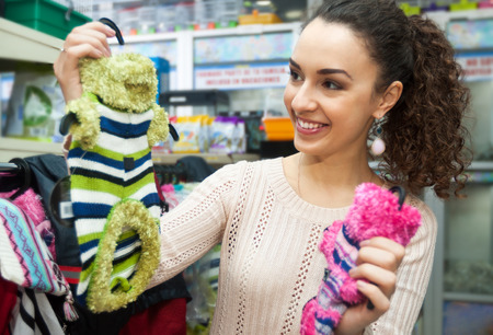 couture: Young woman buying canine couture and smiling in pet store Stock Photo