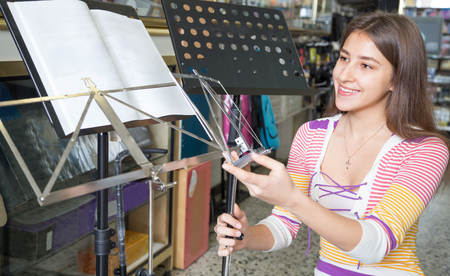 Happy girl changing music stand in music instruments studio
