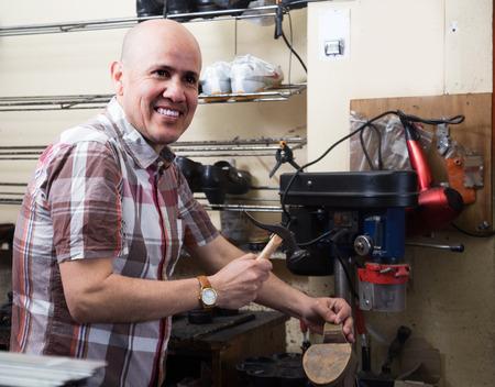 broaching: Professional male shoemaker stitching footwear on machine in shoe atelier Stock Photo