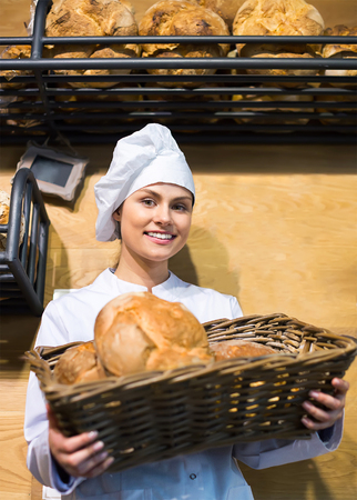 shopgirl: young shopgirl working in bakery with bread and different pastry