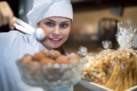 shopgirl: Happy shopgirl working in bakery with different pastry