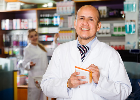 Smiling man pharmacist in  chemists shop Stock Photo