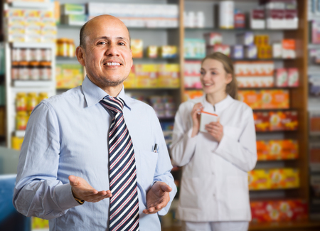 Smiling mature pharmacist and pharmacy technician posing in drugstore Stock Photo