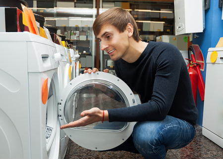 man laundry: Happy young man choosing new laundry machine in supermarket