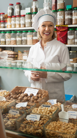 Friendly mature female seller near sacks of beans in local shop Stock Photo
