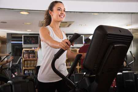 elliptical: Positive female training on elliptical trainers in fitness club Stock Photo