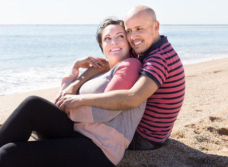 german ethnicity: elderly man with a woman sitting on sand on beach at sunny day