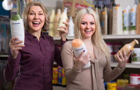 mature mother and adult daughter in good spirits selecting shampoo in the store