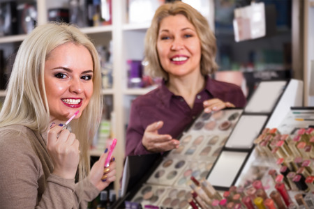 Mature mother and happy daughter buying lipstick  in makeup section