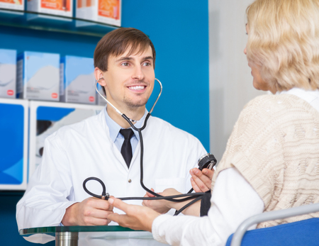 Young male pharmaceutist taking mature patients blood pressure using  sphygmomanometer in pharmacy drugstore