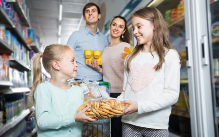 Middle-class young family of four doing shopping in hypermarket Stock Photo