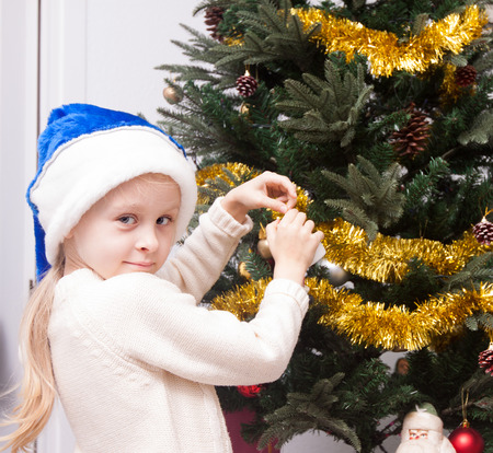 5s: blond girl decorates a Christmas tree