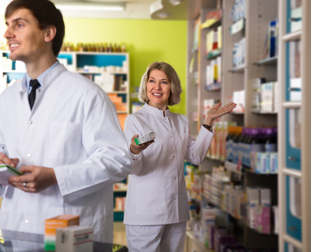 farmacy: Portrait of two caring pharmacists working in modern farmacy