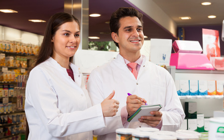 dispensary: Pharmacists at the pharmacy. Smiling woman and a man with a notebook in the hands of a white coat.