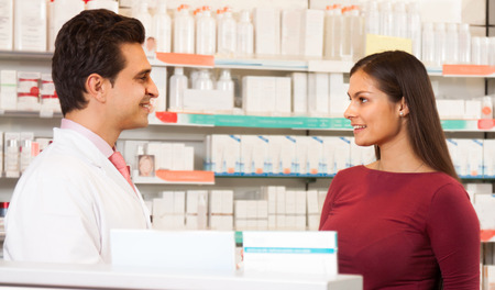 communicates: Pharmacist man in a white robe in the pharmacy communicates with the visitor