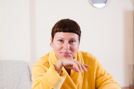 woman bathrobe: Woman in yellow bathrobe at home Stock Photo