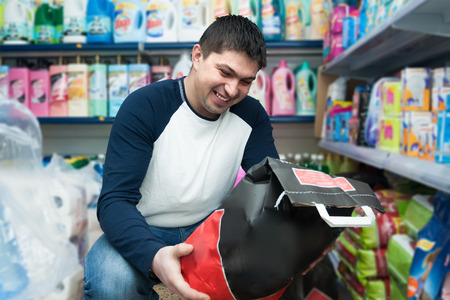 Ordinary middle class dark-haired guy purchasing coal at supermarket