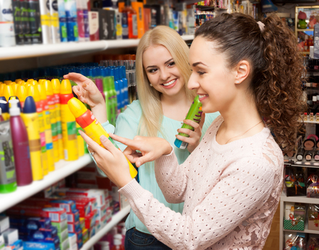 Two young women choosing hair styiling mousse and smiling
