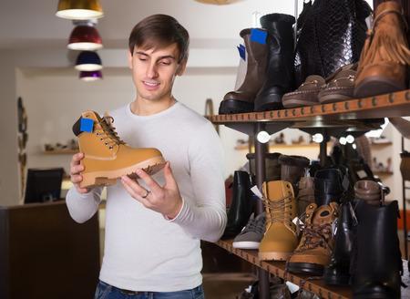 comprando zapatos: El hombre joven la compra de zapatos de invierno en una tienda de zapatos Foto de archivo