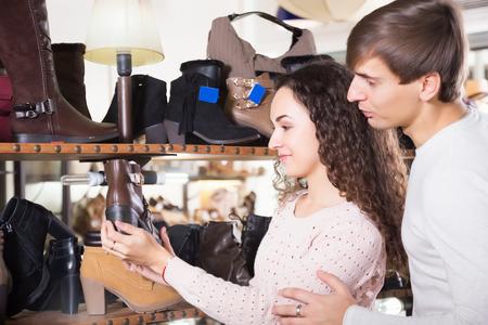 comprando zapatos: Sonriendo hombre y mujer jóvenes de compra zapatos de invierno en una tienda de zapatos