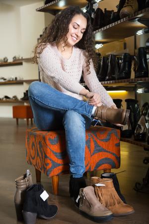 comprando zapatos: Happy female buying winter women shoes in a shoe store Foto de archivo