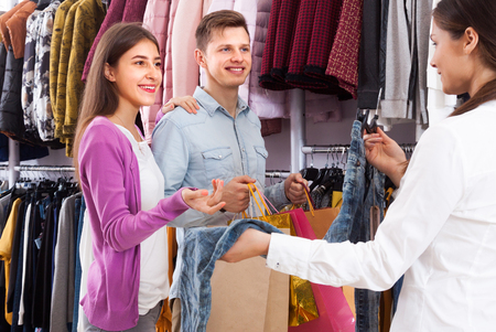 Commesso in un negozio di abbigliamento suggerisce una giovane coppia