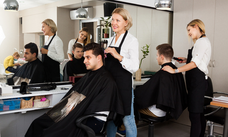 hairdressing saloon: Mature female doing hairstyle for adult man blonde hairdresser serving teenager in hairdressing saloon Stock Photo