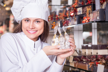 shopgirl selling fine chocolates and confectionery in cafe
