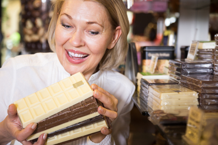 Happy blonde pensioner buying dark and white chocolate in cafe