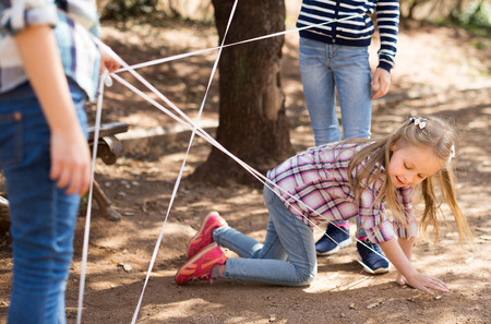children games. Girl gently goes through the tangled rope