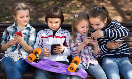 cousin: smiling children playing with the phone on bench outdoors