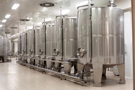 reservoirs: modern Stainless steel wine reservoirs  in a row inside winery