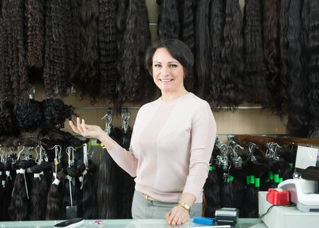 Positive female seller offeringclip-in hair extension at shop  Stock Photo
