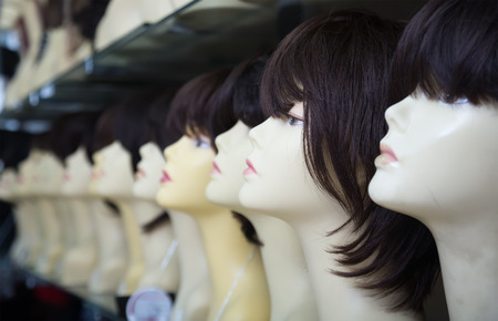 wigs: modern female mannequins with wigs on shelves of hair salon