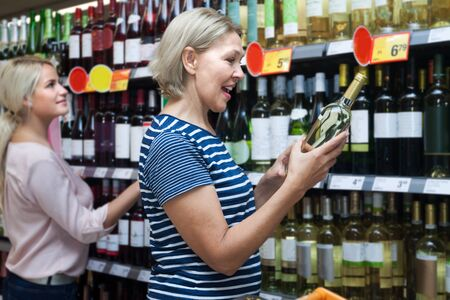 considers: elderly woman housewife considers wine in the supermarket alcoholic division Stock Photo