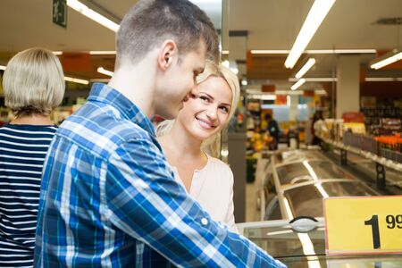 german ethnicity: Positive young couple shopping in supermarket Stock Photo