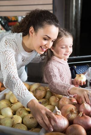 purchasers: Brunette female with a little blonde girl considering bulb onions at store. focus on woman
