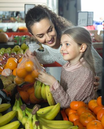 smiling Brunette female with a little blonde girl considering mandarins at store. focus on woman Stock Photo