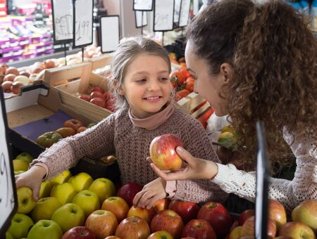 purchasers: mother and smiling daughter buying apples in shop